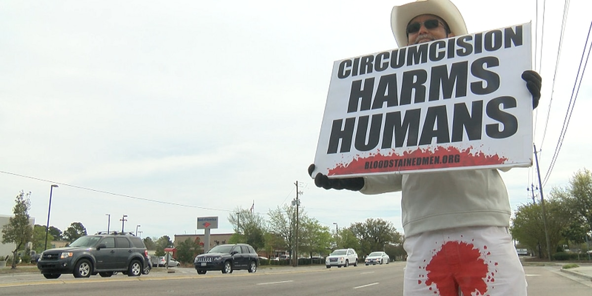 Male circumcision protesters wear bloody pants during demonstration on busy Wilmington road