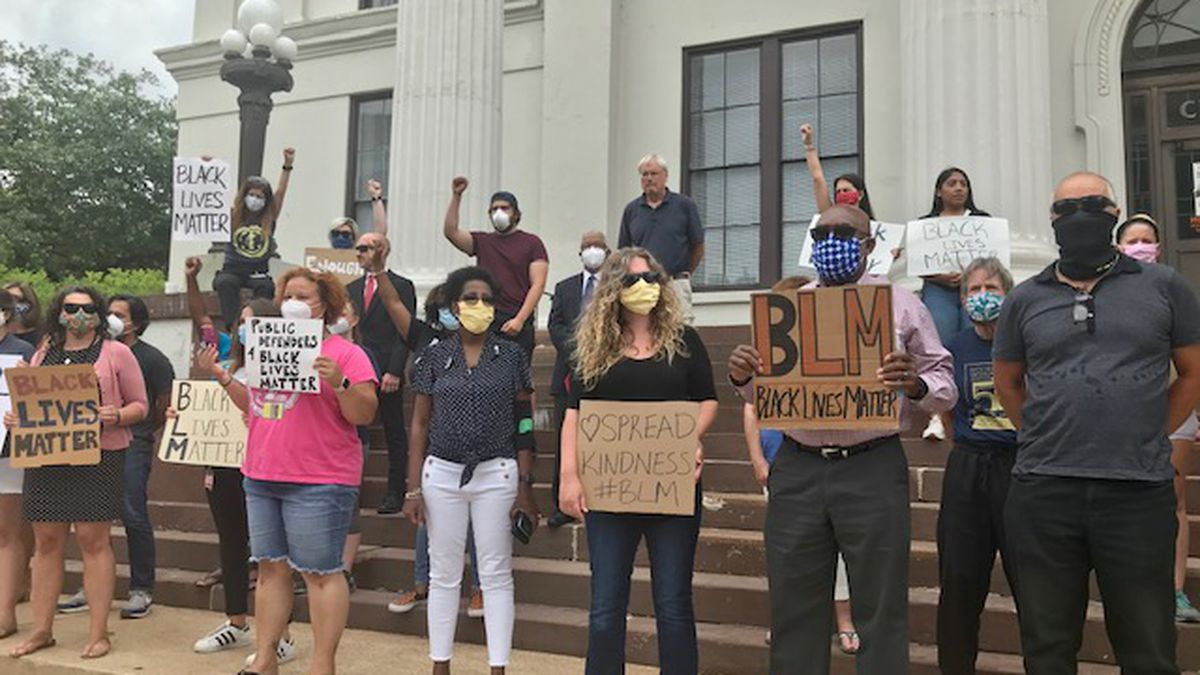 Public defenders hold silent protest on City Hall steps